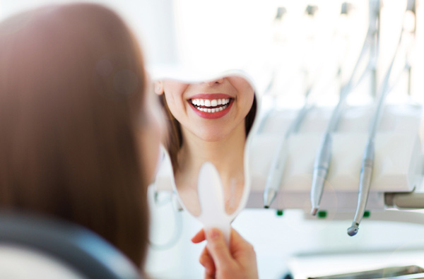 Woman looking at her smile in a mirror after getting dental restoration from D.A. Dental